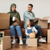 Happy islamic family packing or unpacking boxes