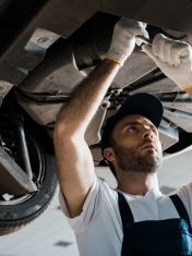 low angle view of serious car mechanic repairing automobile in car service